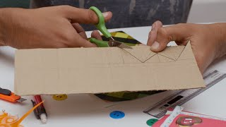 Close up shot of a boy cutting cardboard following pencil line for a craft activity