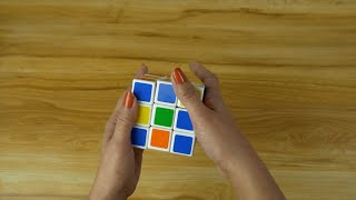 Closeup shot of a woman hands playing with Rubik's cube during leisure time