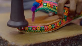 Closeup shot of an Indian worker hands making an ethnic wear sandal for women