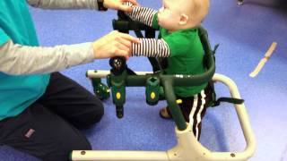 Child with Down syndrome using treadmill and walker at physical therapy