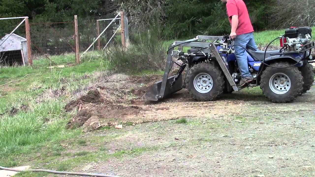 Atv Front End Loader Digging And Scooping Up Dirt And