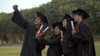 Group of Indian students taking selfies with a smartphone during the convocation ceremony
