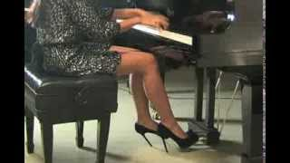 Sexy girl plays the piano in very high heels and short skirt