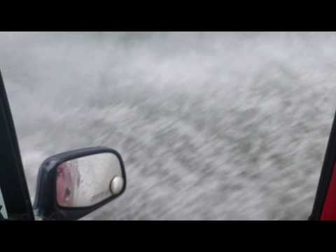Car spraying rain water on road in slow motion