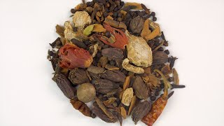 Rotating top view shot of a mixture of traditional Indian spices on a plain white surface