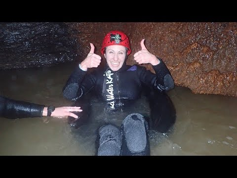 Debbie shimmies into a black rubber wetsuit, dons a helmet and goes tubing