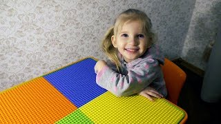 Alina and Daddy assembling the colorful lego table with sandpit orange and green