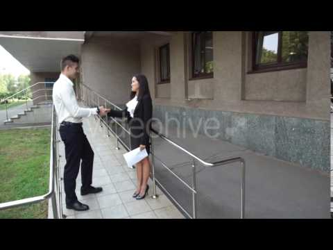 Young Beautiful Asian Business Woman Female and Caucasian Male Shake Hands Talk on Office Building