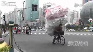Guy struggles to ride overloaded bike on road Thumbnail