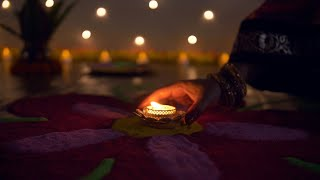 Bokeh shot of an Indian female decorating rangoli with a glowing oil lamp - Diwali decorations