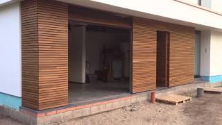 Houten sectionaaldeur en voordeur met gevelbekleding