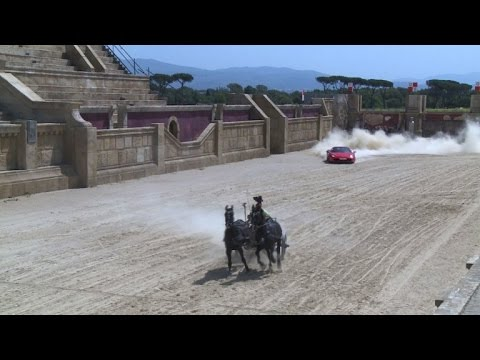 Ferrari driver competes with Roman chariot drawn by horses