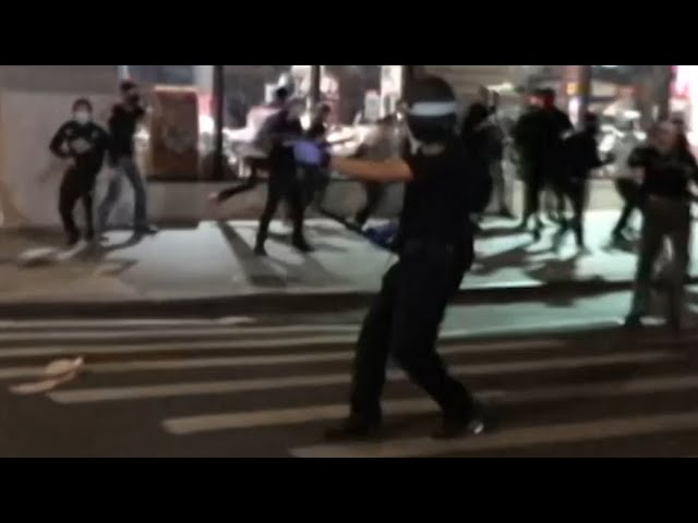 Police officer points gun at crowds in New York