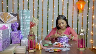 A young beautiful lady happily writing messages for Diwali gifts - festive background