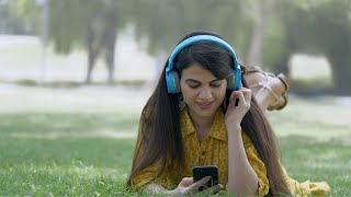 Attractive Indian girl listening and humming her favorite music - leisure time