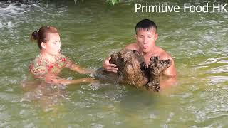 Primitive life : meet big fish by the stream, smart girl catch fish while taking a bath