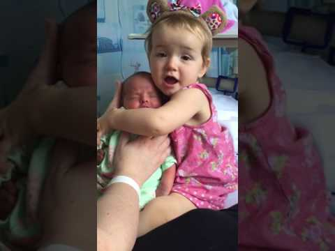 Cute toddler holds baby sister for the first time