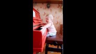 Маленькая девочка играет на фортепиано)