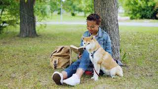 Pretty African American girl student is reading book sitting in park on lawn while her well-bred dog
