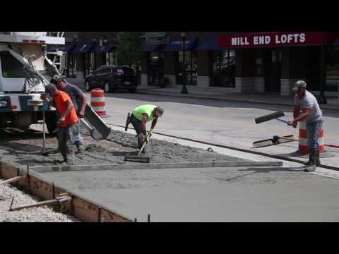 Construction workers pour cement for new parking spaces on N. Water Street