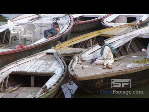 Man eating on docked boats in the Ganges River