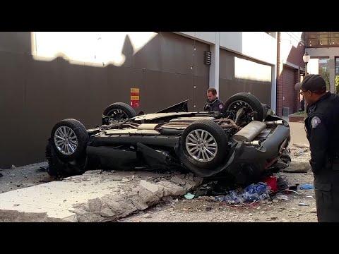 Two die when vehicle plunges off parking garage