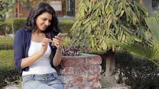 A beautiful girl sitting outside in a lawn on a bright sunny day smiling while scrolling the screen of her Phone