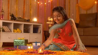 Diwali festival decoration - A cute happy girl decorating rangoli with Diya. Colorful house