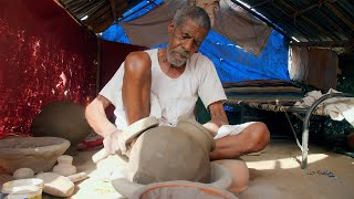A poor potter beating earthen jar to make a water pot