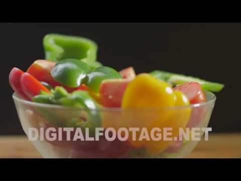 CLIP #1003 / Fresh vegetables falling in an empty glass bowl.