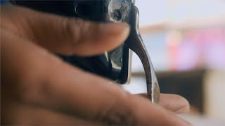 Closeup shot of a blurred tailor puts yellow fabric on a manual sewing machine