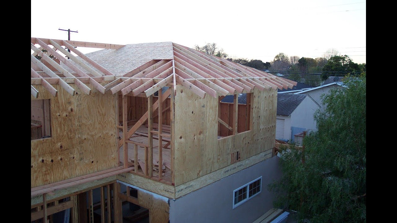 Roof framing soffit connection for home addition with sloping roof