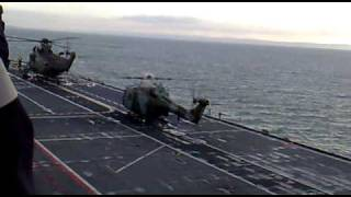 2 Lynx helicopters and a Sea King take off from deck of HMS Illustrious.