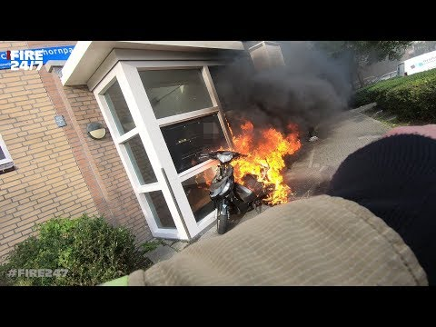 Scooter in de Brand en staat tegen een portiek van een flat aan.