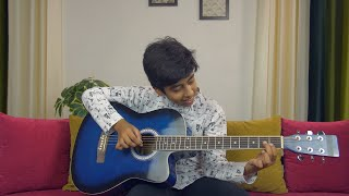 Young talented boy doing music rehearsals on a blue acoustic guitar