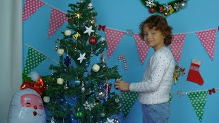 Cute Indian boy decorating a Christmas tree at home on a calm winter evening
