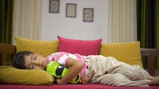 Young innocent child sleeping with his toy car on a couch - concept of childhood