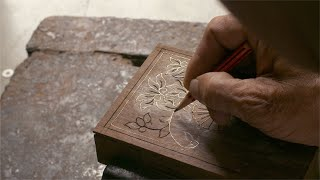 Tarkashi - A craftsman making the design on a wooden box with a pencil