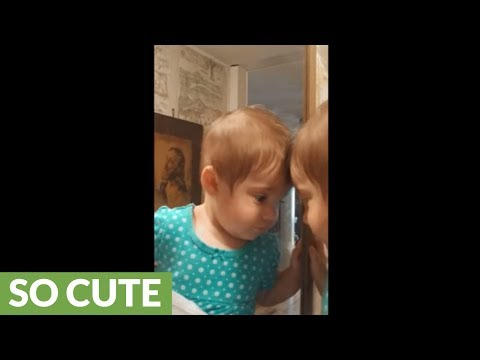 Sweet baby shares kisses with her reflection