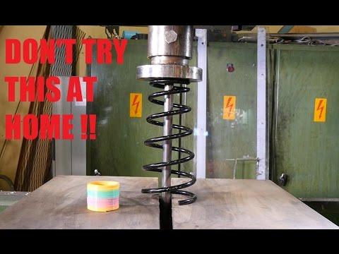 Crushing car spring with hydraulic press