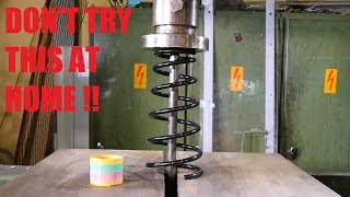 Crushing car spring with hydraulic press