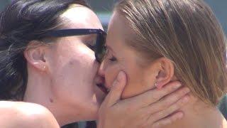 female james bond kissing random girls at the beach