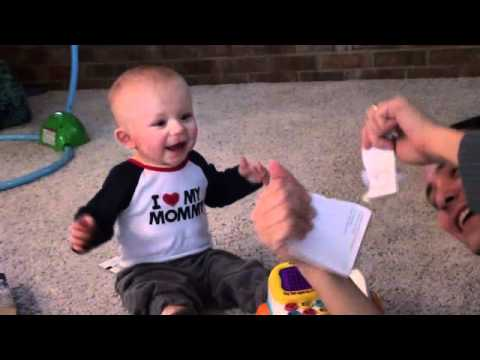 baby laughs at tearing paper