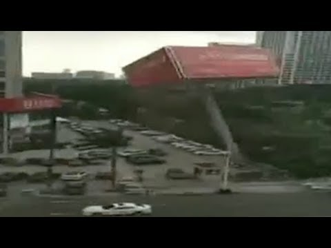 Billboard falls in parking lot, damaging cars