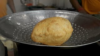 Bhaturas being taken out of the oil after deep frying