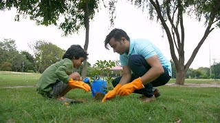 Young Indian man helping his son in planting a sapling in a city park - leisure concept