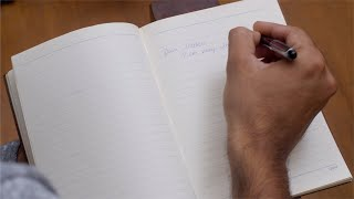 Closeup of male writing a message to his friend in a diary