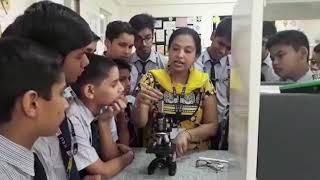 Teacher explaining microscope in science lab @suraj school sec 75