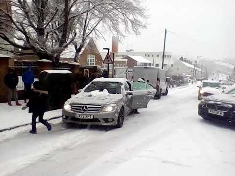 People try to push-start cars on a hill as snow hits London