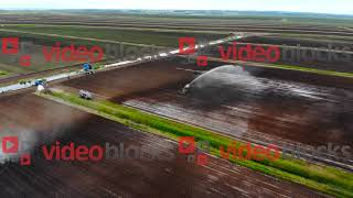 Aerial shot of industrial machines watering and irrigating